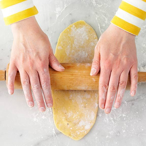 Rolling out homemade pasta dough with a rolling pin.