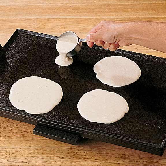 Pouring homemade pancake batter to cook pancakes.