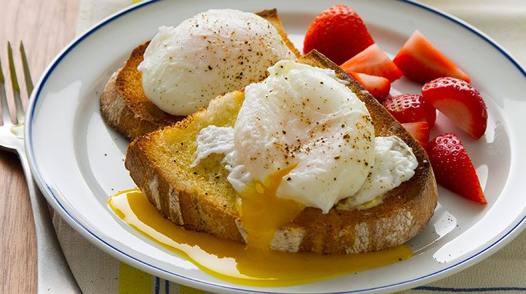 poached eggs sitting onto toast with their centers leaking out over the side and with cut strawberries on the right