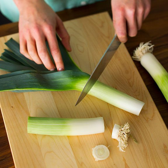 person slicing the ends off of several leeks using a knife