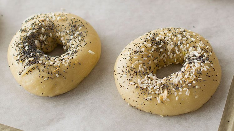 Two fresh, everything bagels sitting side-by-side on parchment paper