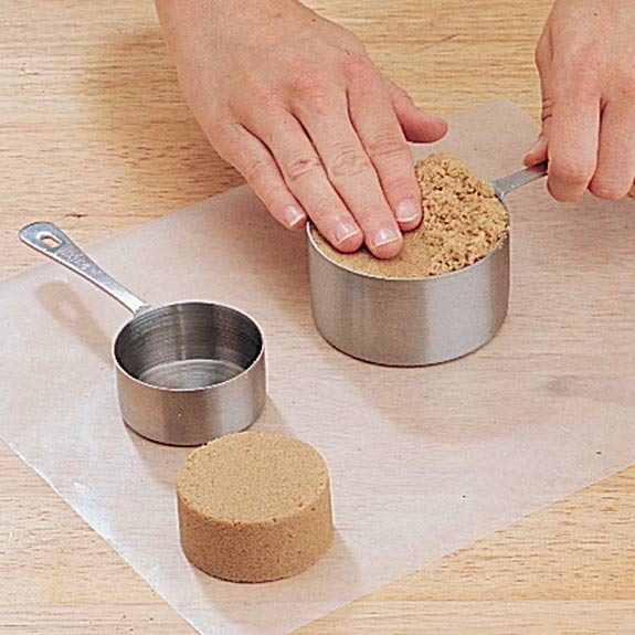 Packing brown sugar to measure the correct amount.
