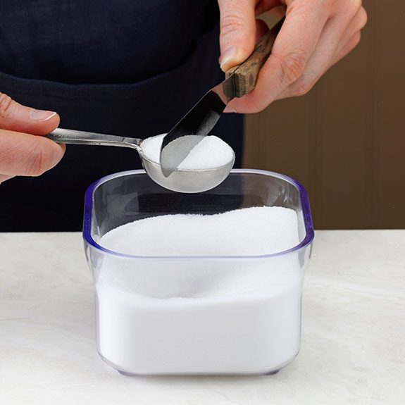 Leveling a measuring spoon over a container to catch spills.