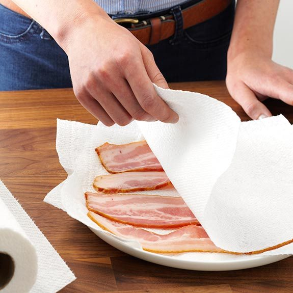 Covering bacon with one or two sheets of paper towel before microwaving.