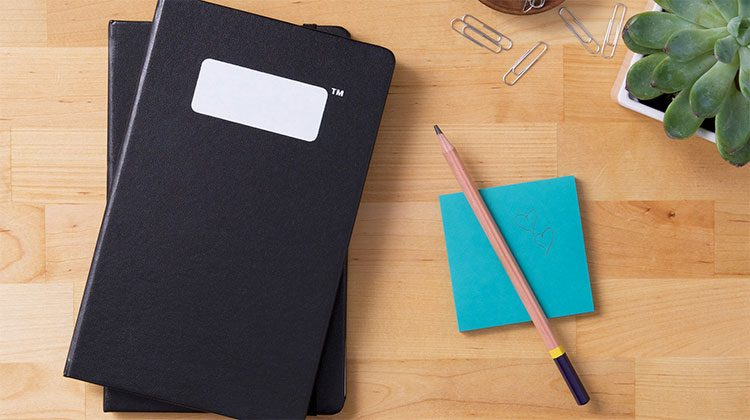 Two black cover notebooks on top one another next to blue post-its and a pen on a wooden countertop