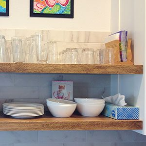 Two layers of wooden shelving installed on a kitchen wall and lined carefully with stacked glasses, bowls, and plates