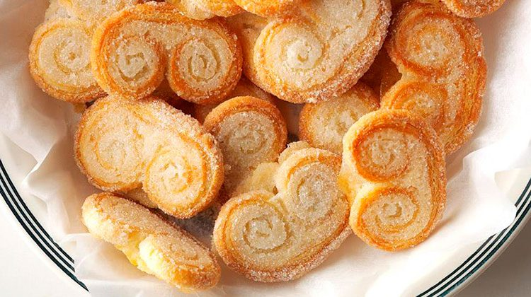 palmiers piled onto a white plate with several stripes around the rim