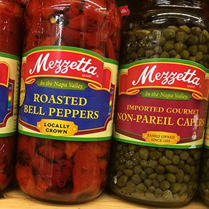 Jars of red bell peppers and capers side-by-side on a shelf
