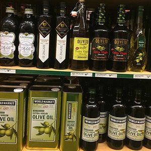 Shelves of different olive oils in bottles and boxes