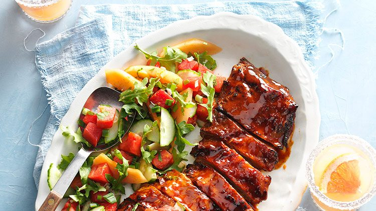 Grilled ribs lined up on a plate beside a small chop salad and two glasses of punch