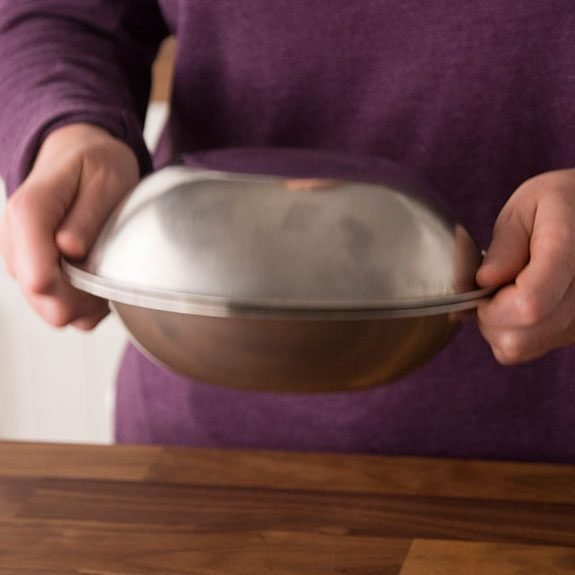 Covering a bowl containing smashed garlic with another bowl to shake.