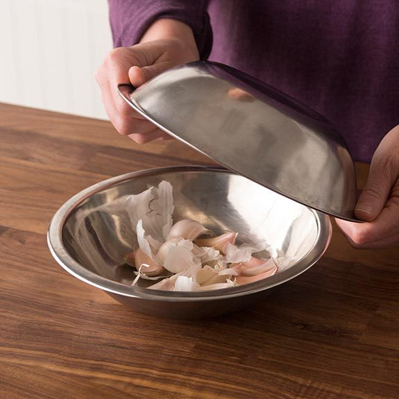 Removing garlic's outer layer by shaking inside two bowls.