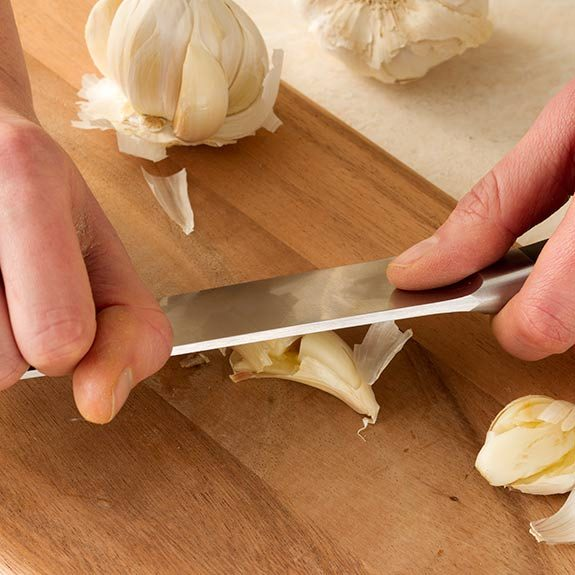 Smashing garlic cloves with a chef's knife before peeling.
