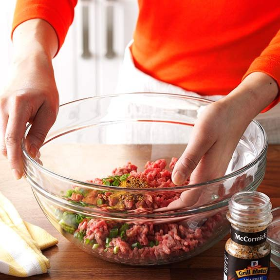 Hand mixing ground beef and seasonings for burger patties.