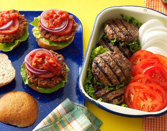 Grilled hamburger patties topped with tomatoes, onions, salsa and lettuce on a blue tray.