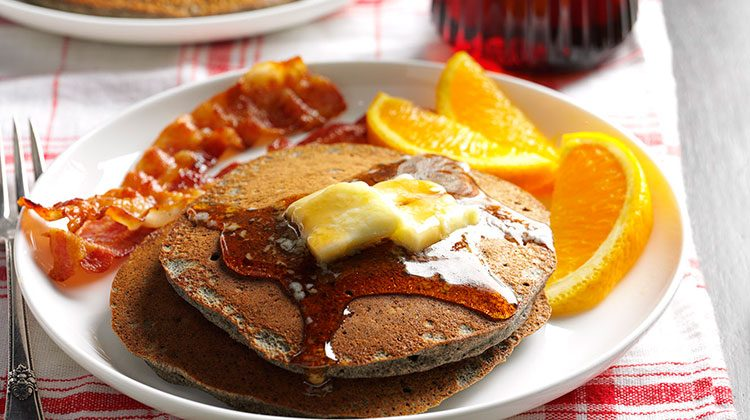 Pancakes covered in butter and syrup beside orange slices