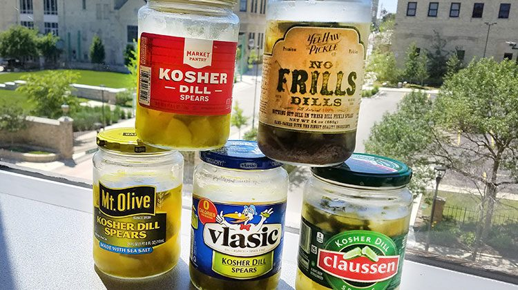 5 jars of different pickle brands stacked in a pyramid shape in front of a large window