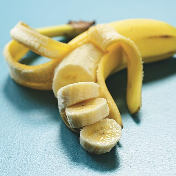 One half-peeled ripe yellow banana partially cut into slices.