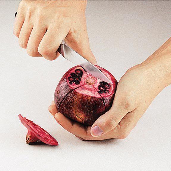 Scoring a pomegranate into quarters.