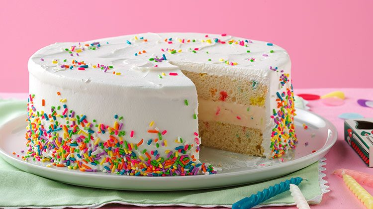 White frosted cake with its bottom half covered in colorful sprinkles