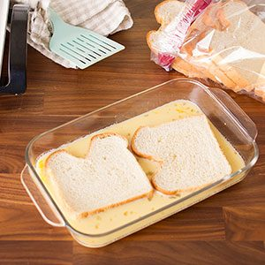Two slices of bread laying flat in the glass pan to soak up the custard