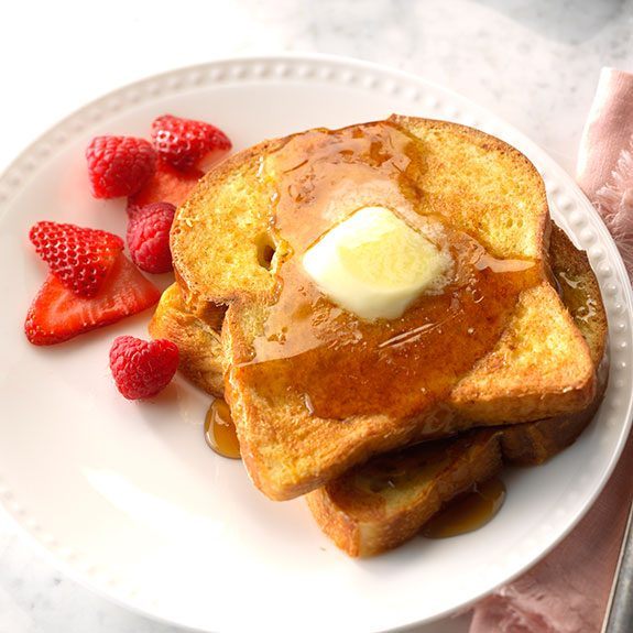 Two slices of french toast drizzled with maple syrup and topped with butter