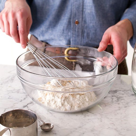 Person mixing dry ingredients together in a large glass bowl