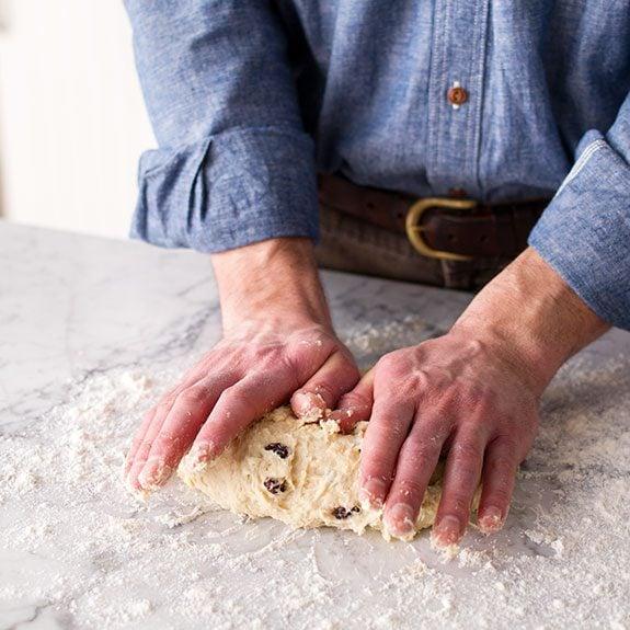 Person kneading soda bread dough out on a floured countertop