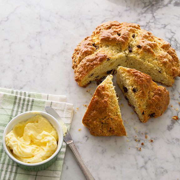 Loaf of Irish soda bread with several wedge cuts from it sitting pulled apart from the circle and butter on the side
