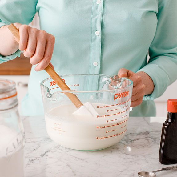 person stirring ingredients together in a large glass bowl