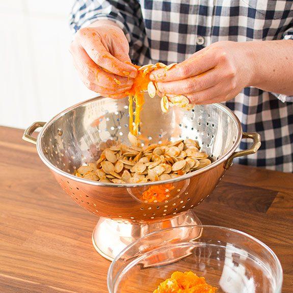 Person separating pumpkin seeds from orange gunk in a metal bowl