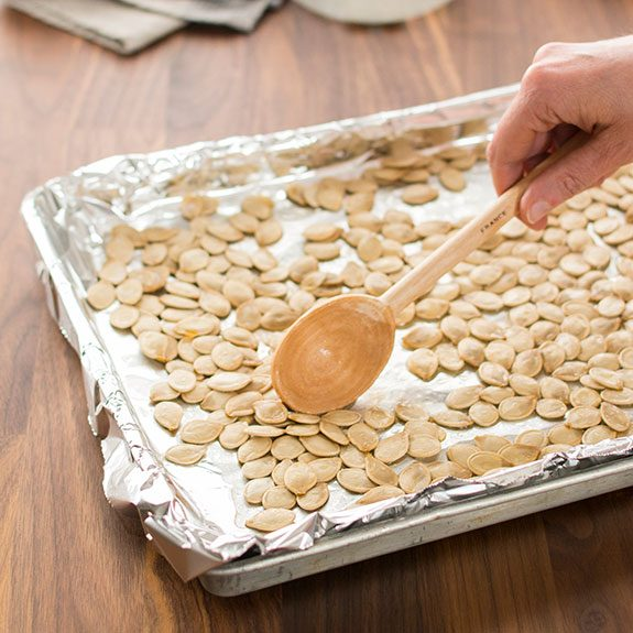 Person using a wooden spoon to stir pumpkin seeds on a baking sheet lined with foil