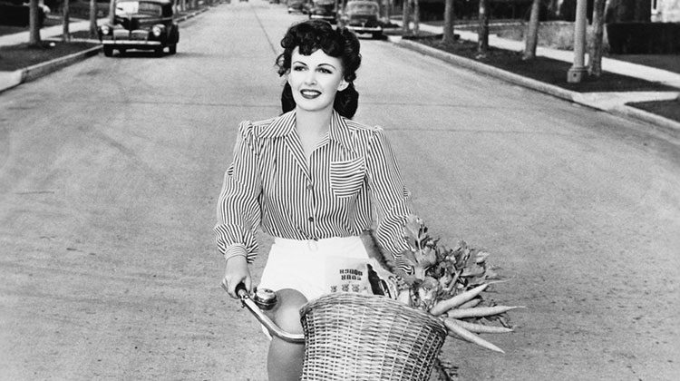 Black and white photograph of a woman riding down a street on a bicycle with a basket full of produce