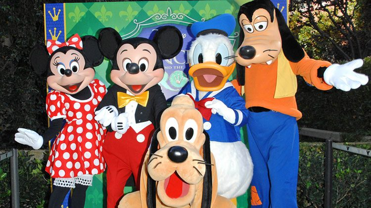 Minnie, Mickey Mouse, Donald Duck, Goofy and Pluto all posing for a picture in front of a Princess and the Frog backdrop