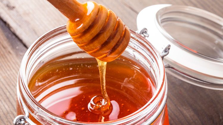 A honey stick being pulled from a jar while the honey drips back down slowly