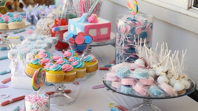 Table filled with glass platters holding pink and blue frosted cupcakes, cake pops, and other assorted candies in glass jars