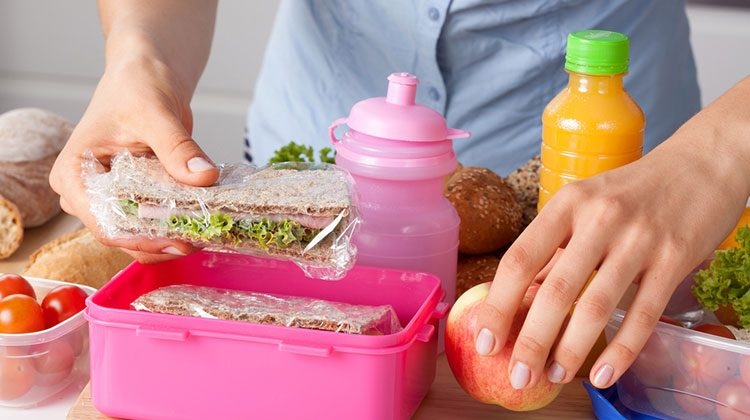 Person packing an apple and sandwich into a pink lunch box with the ingredients used to make the sandwich still laying out on the counter around them
