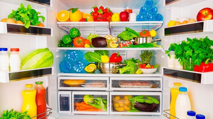 Double-door fridge open wide and filled to the brim with fresh vegetables, fruit, bottles of water and jugs of milk