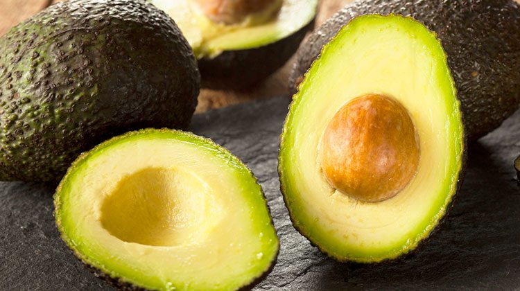 Avocados piled together with one sliced in half and propped up to reveal its insides to the viewer