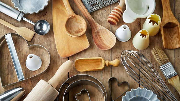 Kitchen tools of all shapes and sizes spread out in an organized mess on a wooden counter