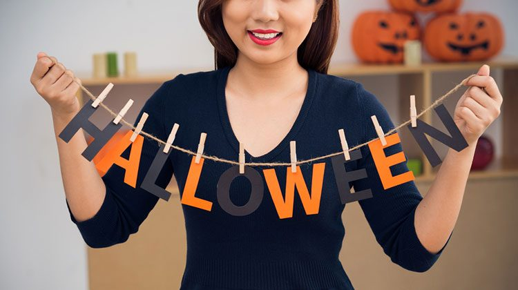 Smiling woman holding up a rope with clips holding up orange and black letters spelling out 'HALLOWEEN'