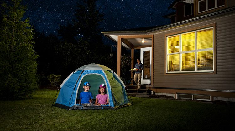 Boy and a girl in a tent in the backyard under a starry sky. They are kneeling at the entrance to the open tent as their mother is coming out of their nearby house with snacks in hand