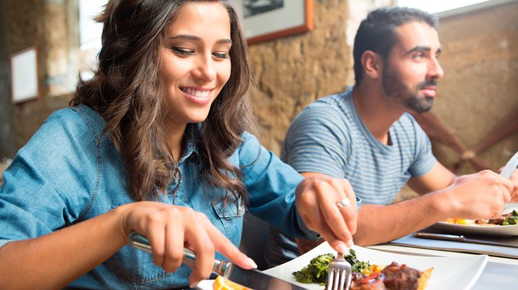 Woman wearing a denim jacket digging into a meal at a resturant with beige walls. The man in a blue striped shirt to her left is staring ahead, utensils in hand
