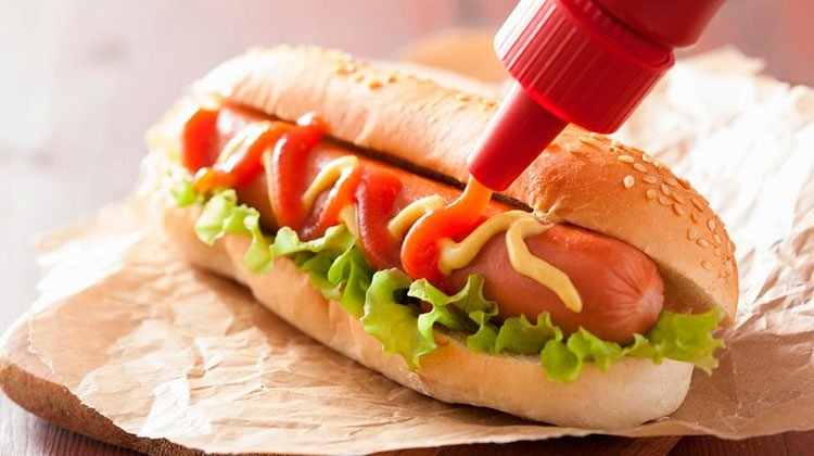 Bottle of ketchup squirting a serpentine line across a hotdog