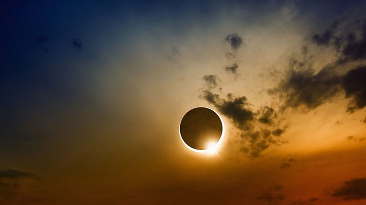 Solar eclipse set on a beautiful sunset with oranges and yellows illuminating small clouds and dark blue hues bordering the scene