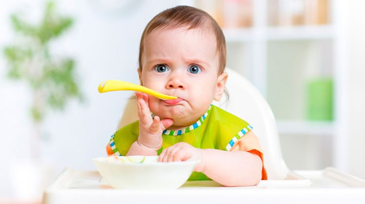 Frowning baby with a yellow spoon sticking out of their mouth. One hand is reaching up to hold their chin and the other is reaching into their white bowl on the tray of their high chair