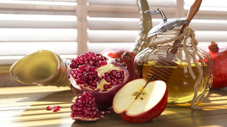 Sliced pomegranate and apple beside a jar of honey with a stir-stick and a horn in the background