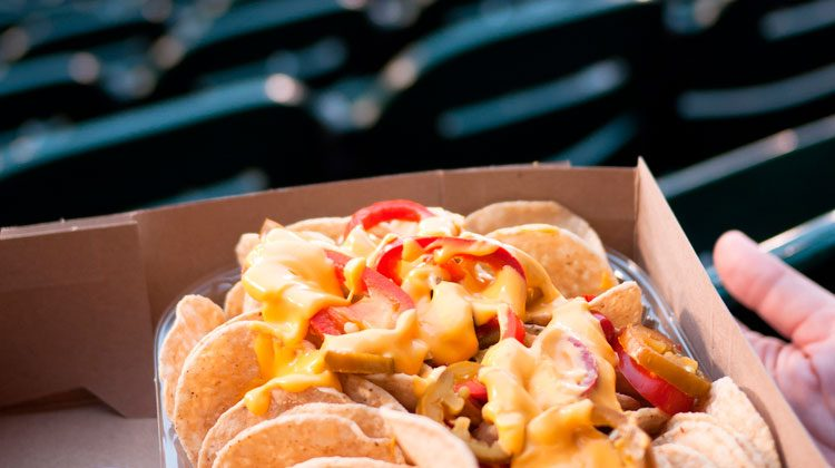 Person holding loaded nachos while sitting on the bleachers of a baseball field