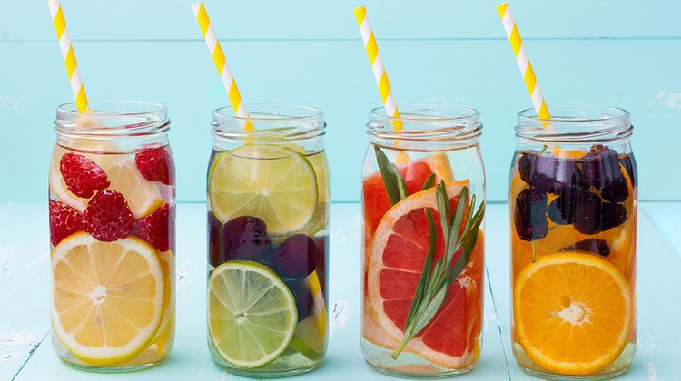 Four glass jars each with a different combination of sliced fruit and whole berries plus yellow-striped straws
