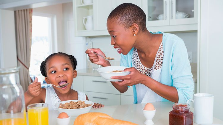 Mother eating cereal with her daughter at the breakfast table